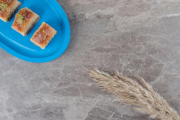 Kleine portie turkse bakhlava's en verengrasstengels op marmeren oppervlak