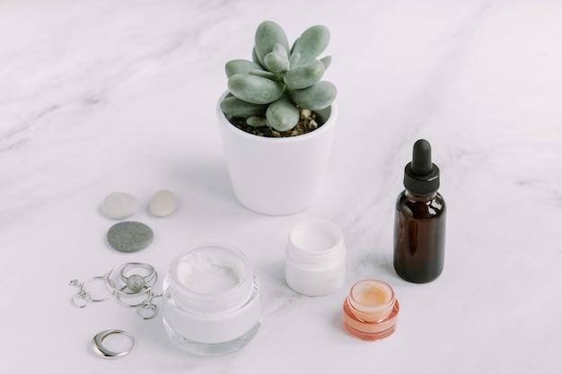 Kleine potjes gezichtscrème en verjongende serumfles palmboomblad schoonheid en spa-concept
