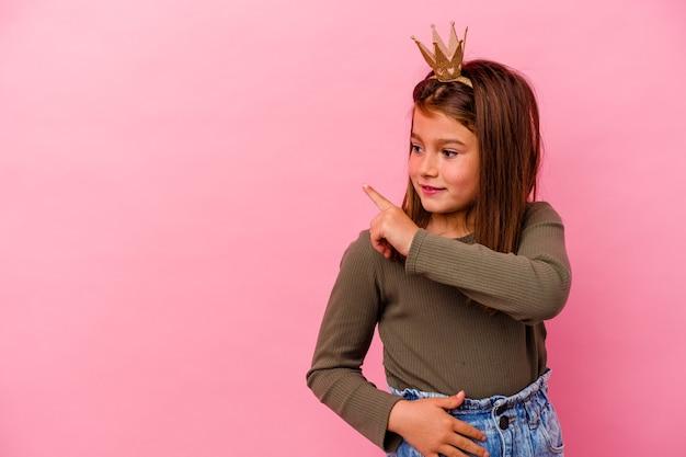 Kleine prinses meisje met kroon geïsoleerd op roze achtergrond glimlachend en opzij wijzend, iets tonen op lege ruimte.