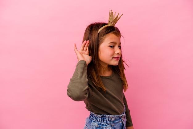 Kleine prinses meisje met kroon geïsoleerd op roze achtergrond proberen te luisteren naar een roddel.