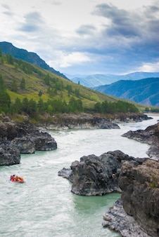 Kleine rafting boot in snelle bergrivier tussen rotsen