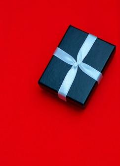 Kleine rechthoekige zwarte geschenkdoos op een rode achtergrond