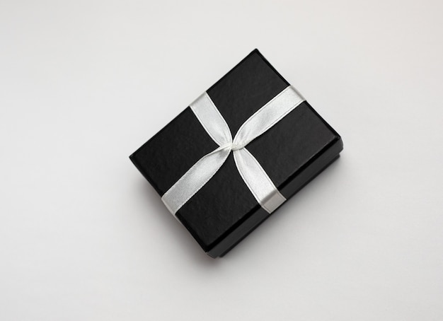 Kleine rechthoekige zwarte geschenkdoos op een witte achtergrond