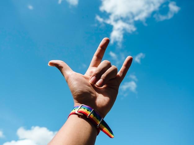 Kleine regenboogvlagriem op de pols van homo's met ik hou van je vingerteken dat omhoog gebaart naar de blauwe hemelachtergrond. lgbt-concept met trotskleuren en regenboogvlagstrook.
