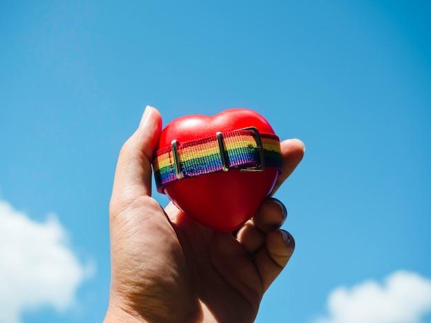 Kleine regenboogvlagriem op rood hartbal in vrolijke mensenhand op blauwe hemelachtergrond. lgbt-concept met trotskleuren en regenboogvlagstrook.