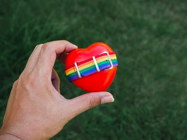 Kleine regenboogvlagriem op rood hartbal in vrolijke mensenhand op groene aardachtergrond. lgbt-concept met trotskleuren en regenboogvlagstrook.