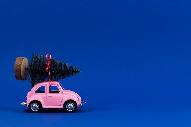 Kleine retro roze speelgoedauto met kerstboom