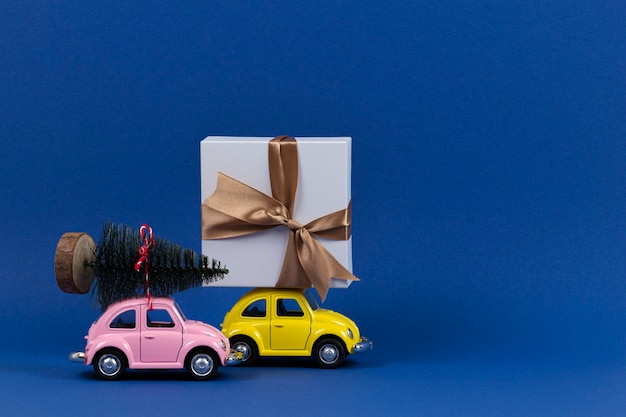 Kleine retro speelgoed modelauto's met huidige geschenkdoos en kleine kerstboom op marineblauw