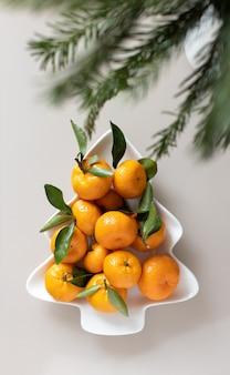 Kleine rijpe mandarijnen met bladeren, op plaat in de vorm van een kerstboom op beige achtergrond. concept winter vitamine voedsel. humeurige stilleven feestelijke compositie. voor wenskaart, boek, verhalen.