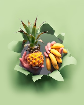 Kleine rijpe oranje ananas, tros kleine bananen in de hand. handen met het fruit komen tevoorschijn uit gescheurd papiergat