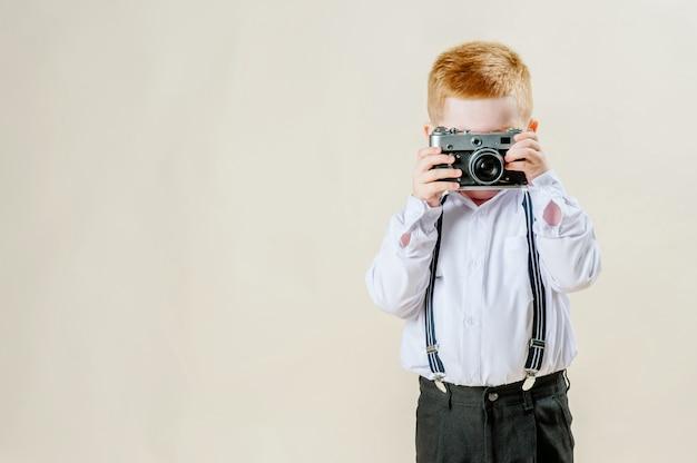 Kleine rode haired jongen met een retro camera in handen op een geïsoleerde lichte muur