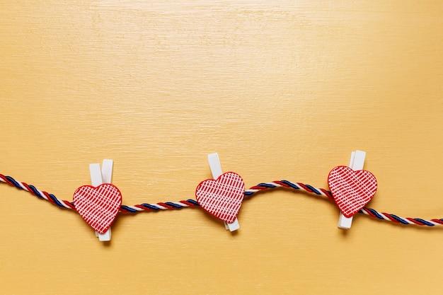 Kleine rode harten op beige houten achtergrond. valentijn concept
