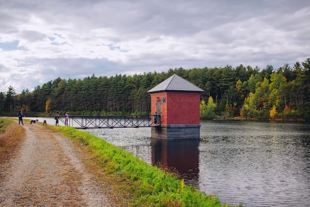 Kleine rode hut gebouwd op een rivier en verbonden met een brug met een prachtig natuurlijk landschap