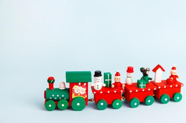 Kleine rode kerst speelgoed trein op blauwe achtergrond