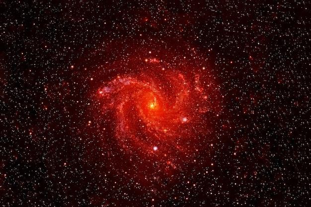 Kleine rode melkweg op een donkere achtergrond. elementen van deze afbeelding zijn geleverd door nasa. hoge kwaliteit foto