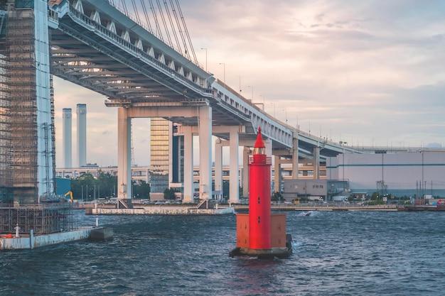 Kleine rode metalen vuurtoren onder yokohama-brug voor industriële en transportveiligheid.