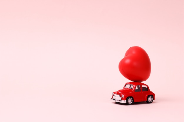 Kleine rode retro speelgoedauto met hart op het dak op roze valentijnsdag huidige levering concept