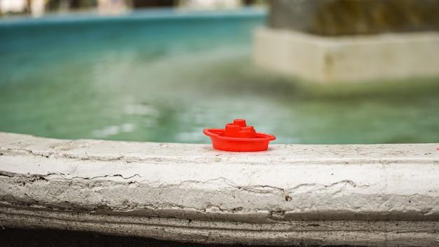 Kleine rode speelgoedboot die op de rand van een oude fontein staat vergeten speelgoed