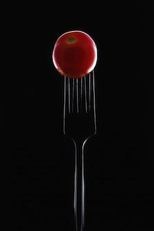 Kleine rode tomaat op een vork op een zwarte achtergrond