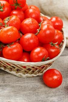 Kleine rode tomaten in een rieten mand op een oude houten tafel. rijpe en sappige kers