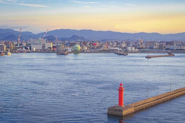 Kleine rode vuurtoren in het midden van de baai van japan voor water voor industrieel en vervoersconcept