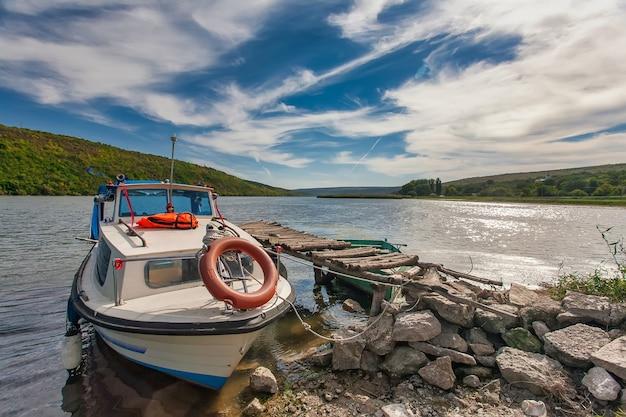 Kleine roeispaan vissersboot afgemeerd op een rivier met reflectie