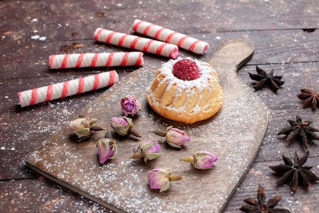 Kleine romige cake met framboos samen met roze stoksnoepjes op bruin houten bureau, snoep zoete suiker bak cake
