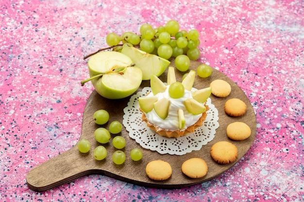 Kleine romige cake met gesneden fruit druiven appels op gekleurde, cake zoete suiker bakken
