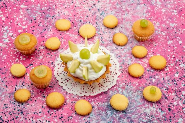 Kleine romige cake met gesneden fruitkoekjes op gekleurd bureau, cakesuiker