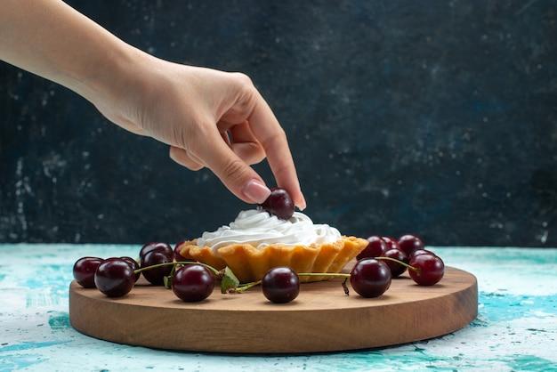 Kleine romige cake met verse kersen op lichtblauw bureau, cakecrème zoete suikerbak
