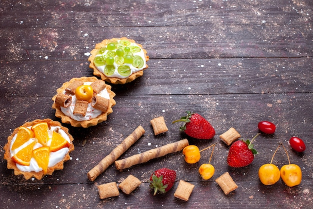 Kleine romige cakes met gesneden druiven sinaasappelen samen met aardbeien op bruin houten bureau, cake biscuit fruit zacht