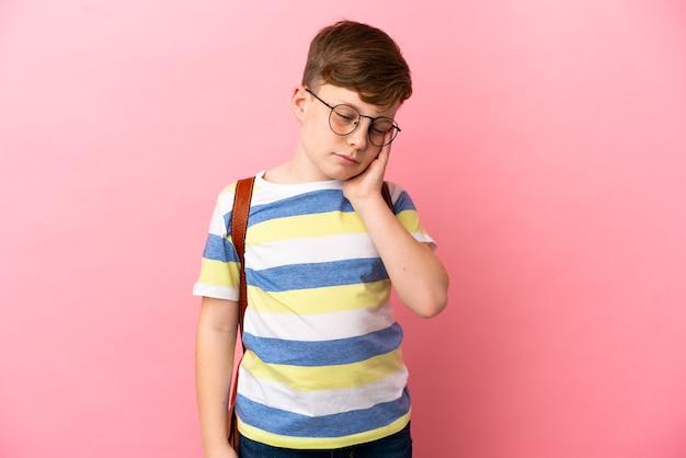 Kleine roodharige blanke jongen geïsoleerd op roze achtergrond met hoofdpijn