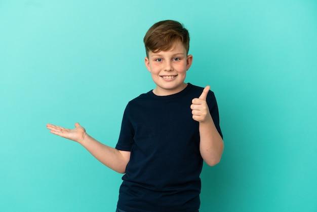 Kleine roodharige jongen geïsoleerd op blauw oppervlak met copyspace denkbeeldig op de palm om een advertentie in te voegen en met duimen omhoog
