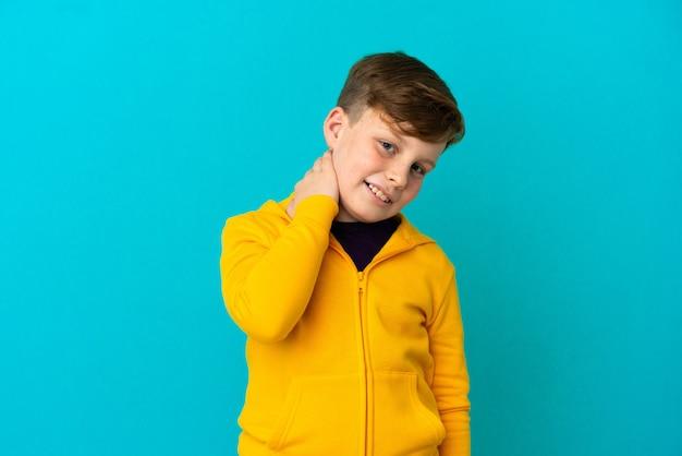 Kleine roodharige jongen geïsoleerd op blauwe achtergrond lachen