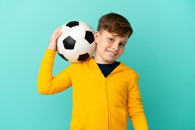 Kleine roodharige jongen geïsoleerd op blauwe achtergrond met voetbal