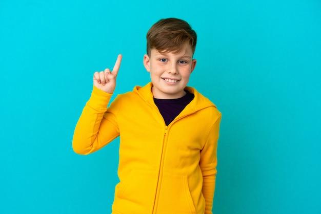 Kleine roodharige jongen geïsoleerd op een blauwe achtergrond die een geweldig idee naar boven wijst