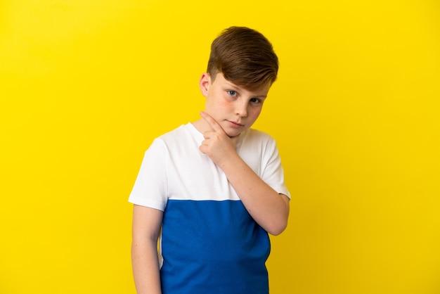 Kleine roodharige jongen geïsoleerd op gele achtergrond denken