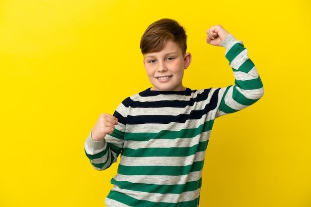 Kleine roodharige jongen geïsoleerd op gele achtergrond die een overwinning viert