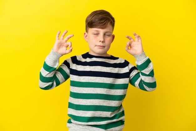 Kleine roodharige jongen geïsoleerd op gele achtergrond in zen pose