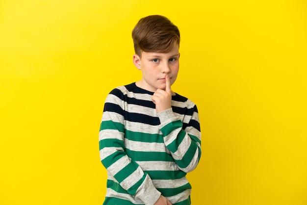 Kleine roodharige jongen geïsoleerd op gele achtergrond met twijfels tijdens het opzoeken