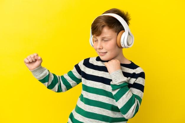 Kleine roodharige jongen geïsoleerd op gele achtergrond muziek luisteren en dansen