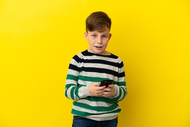 Kleine roodharige jongen geïsoleerd op gele achtergrond verrast en het verzenden van een bericht