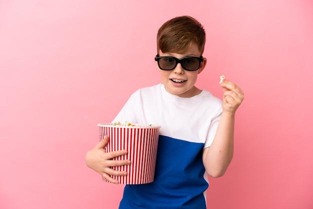 Kleine roodharige jongen geïsoleerd op roze achtergrond met 3d-bril en met een grote emmer popcorns