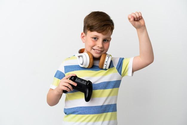 Kleine roodharige jongen met een gamepad geïsoleerd op een witte achtergrond die een overwinning viert