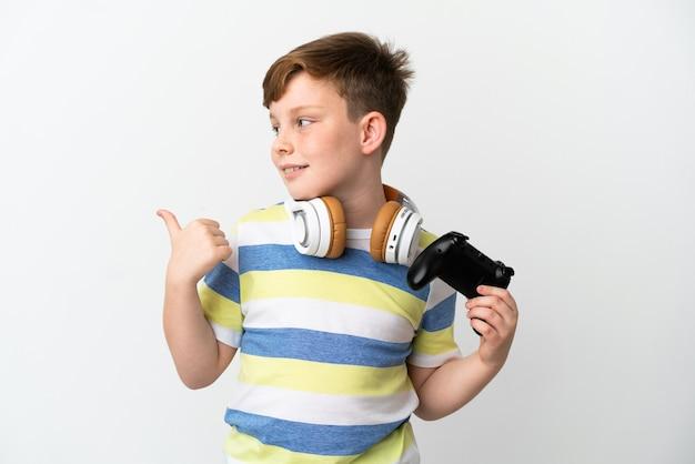 Kleine roodharige jongen met een gamepad geïsoleerd op een witte achtergrond die naar de zijkant wijst om een product te presenteren