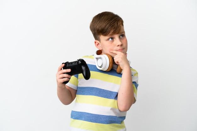 Kleine roodharige jongen met een gamepad geïsoleerd op een witte achtergrond met twijfels