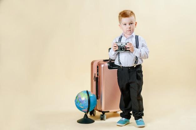 Kleine roodharige jongen met een retro camera in handen