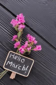 Kleine roze bloemen op een donkere houten ondergrond. bovenaanzicht close-up. hallo maart.