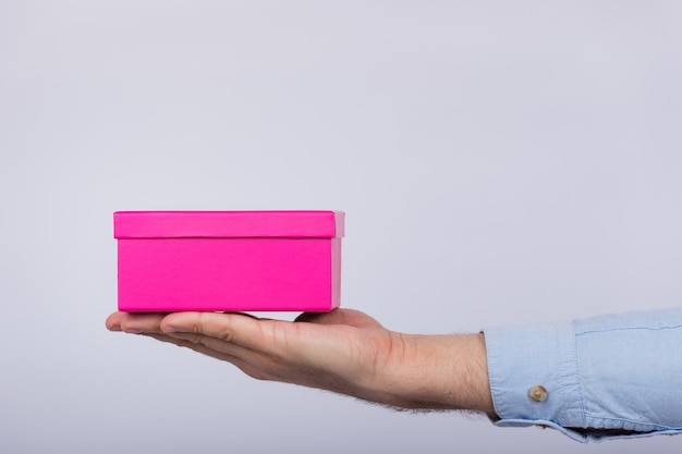Kleine roze doos aan de kant van de jongens. man met geschenkdoos. zijaanzicht