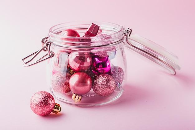 Kleine roze kerstballen in glazen pot